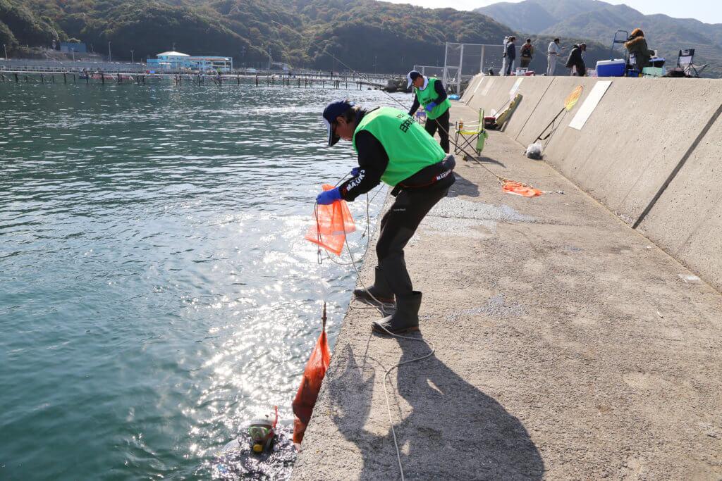 水中のダイバーはメッシュの袋にゴミを回収。ゴミがいっぱいになると陸上のスタッフがカラビナ付きのロープを投げ、引き揚げるという手順で進められた