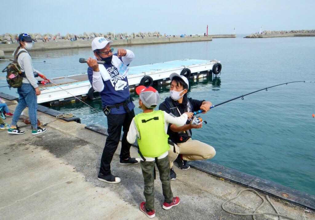 イベント参加者の子供にキャストの方法をレクチャーをするオール阪神さん