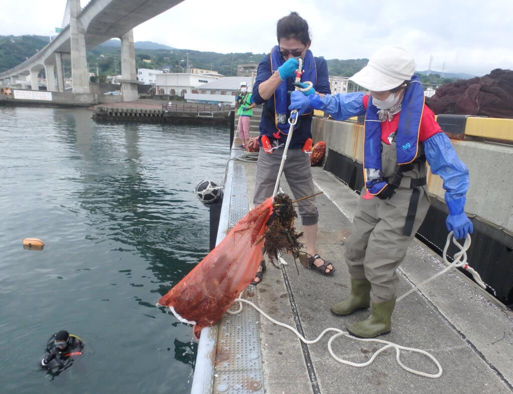 水中ダイバーが集めたゴミを陸上スタッフが引き上げる様子