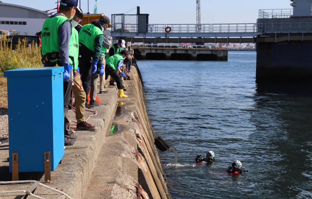 ダイバーが回収した水中のゴミを引き揚げる様子